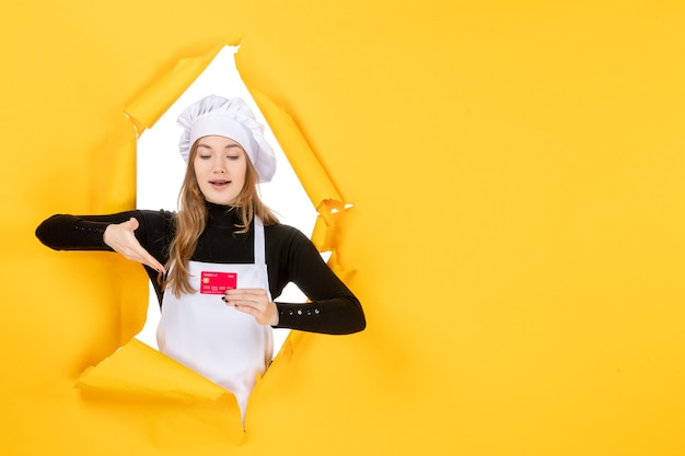 Front view female cook holding red bank card on yellow job photo emotion food kitchen color