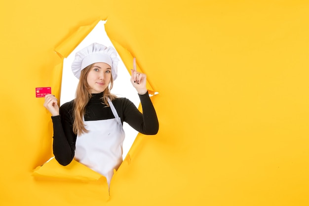 Front view female cook holding red bank card on yellow money color job photo cuisine emotion food