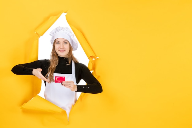 Front view female cook holding red bank card on yellow money color job photo food kitchen cuisine emotion