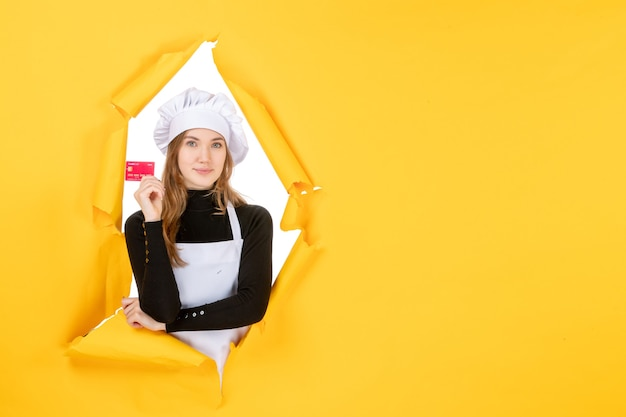 Front view female cook holding red bank card on yellow money color job photo food kitchen cuisine emotions