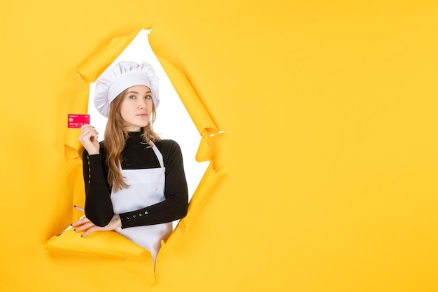 Front view female cook holding red bank card on yellow money color job photo kitchen emotion food