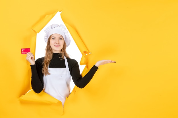 Front view female cook holding red bank card on yellow money colors job photo food kitchen cuisine emotion