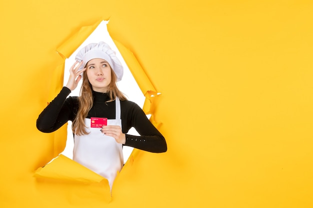 Front view female cook holding red bank card on yellow photo emotion food kitchen cuisine color job