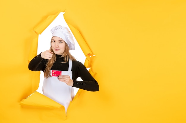Front view female cook holding red bank card on yellow photo emotion food kitchen cuisine color money job