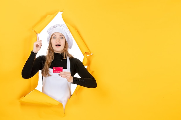 Front view female cook holding red bank card on yellow photo emotion food kitchen cuisine color money