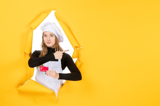 Front view female cook holding red bank card on yellow photo emotion food kitchen cuisine colors money job