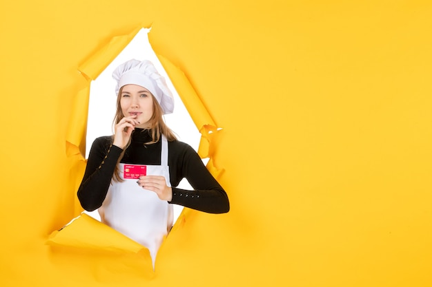 Front view female cook holding red bank card on yellow photo emotion kitchen cuisine color money job
