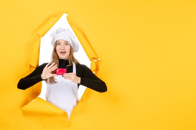 Front view female cook holding red bank card on a yellow photo emotion money food kitchen cuisine color job