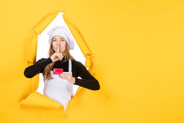 Front view female cook holding red bank card on the yellow photo emotion money food kitchen cuisine color job