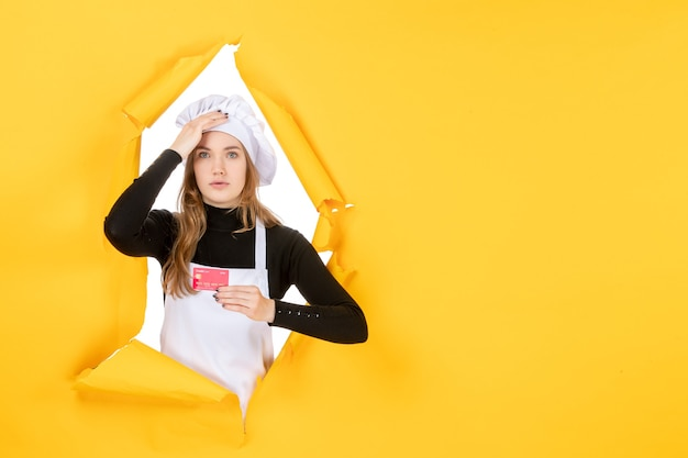 Front view female cook holding red bank card on yellow photo emotion money food kitchen cuisine color