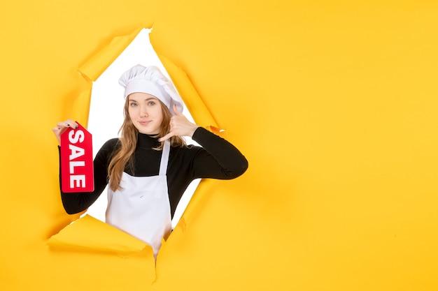 黄色の仕事キッチン料理感情食品写真に赤いセールを書いている正面図の女性料理人