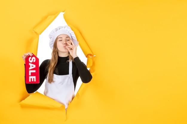 노란색 작업 주방 요리 감정 음식 사진에 빨간색 판매 글을 들고 전면 보기 여성 요리사