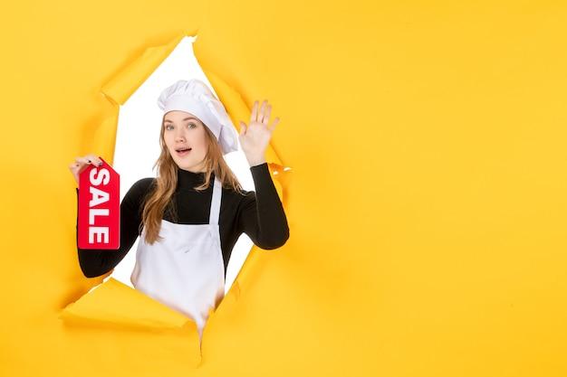 노란색 작업 주방 요리 감정 사진에 빨간색 판매 글을 들고 전면 보기 여성 요리사