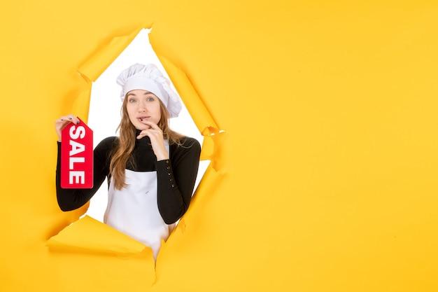 노란색 부엌 감정 사진 요리 작업에 빨간색 판매 글을 들고 전면 보기 여성 요리사