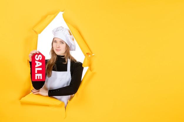 Cuoca di vista frontale che tiene la scrittura di vendita rossa su foto di lavoro di colore giallo cucina cucina emozione cibo