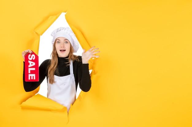 Cuoca di vista frontale che tiene la scrittura di vendita rossa sul lavoro di cucina di emozione della cucina di colore alimentare giallo