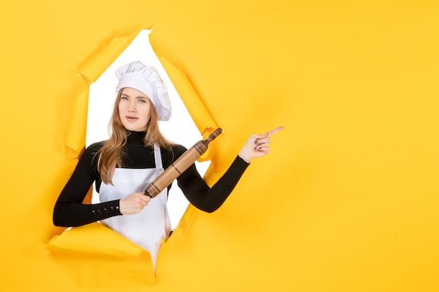 노란색 부엌 작업 요리 음식 사진 감정에 롤링 핀을 들고 전면 보기 여성 요리사