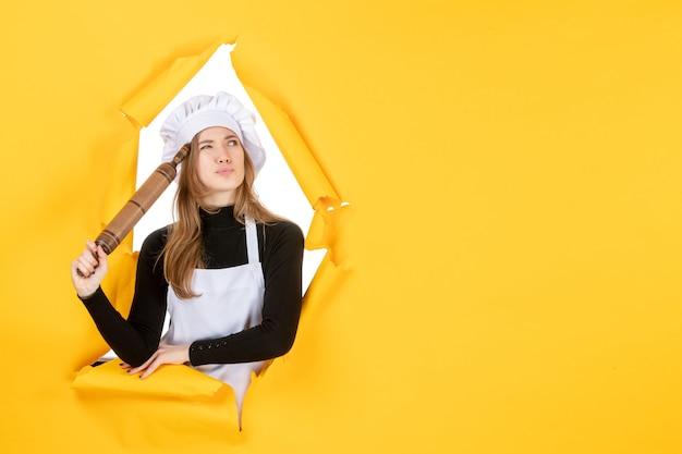 노란색 색상 부엌 작업 요리 음식 태양에 롤링 핀을 들고 전면 보기 여성 요리사 사진