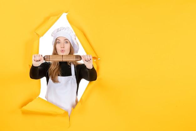 노란색 부엌 작업 색상 요리 음식 태양에 롤링 핀을 들고 전면 보기 여성 요리사 사진