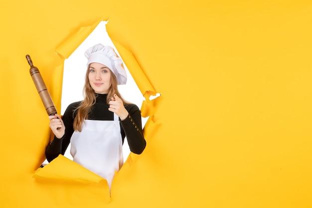 노란색 태양 색상 주방 작업 요리 사진 감정에 롤링 핀을 들고 전면 보기 여성 요리사