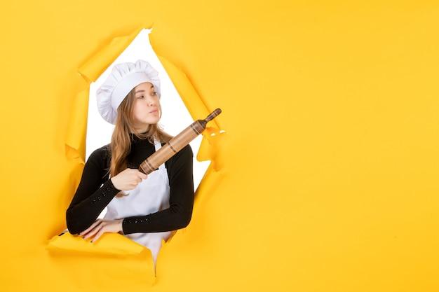 Cuoca di vista frontale che tiene mattarello sul colore giallo lavoro cucina cibo sole foto