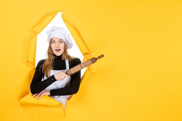 Cuoca di vista frontale che tiene mattarello sul colore giallo cucina lavoro cucina cibo foto