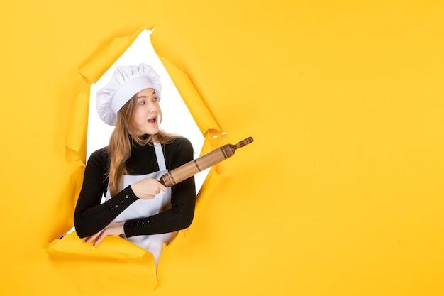 Cuoca di vista frontale che tiene mattarello sul colore giallo cucina lavoro cucina sole foto