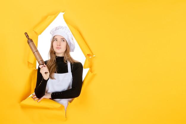Cuoca di vista frontale che tiene mattarello sulla foto del sole della cucina di colore del lavoro della cucina gialla