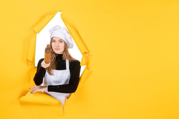 Cuoca di vista frontale che tiene mattarello sulla foto gialla del sole del cibo di colore del lavoro della cucina