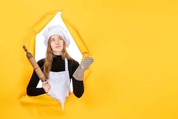 Cuoca vista frontale che tiene mattarello sulla foto gialla cucina lavoro cucina colore cibo sole