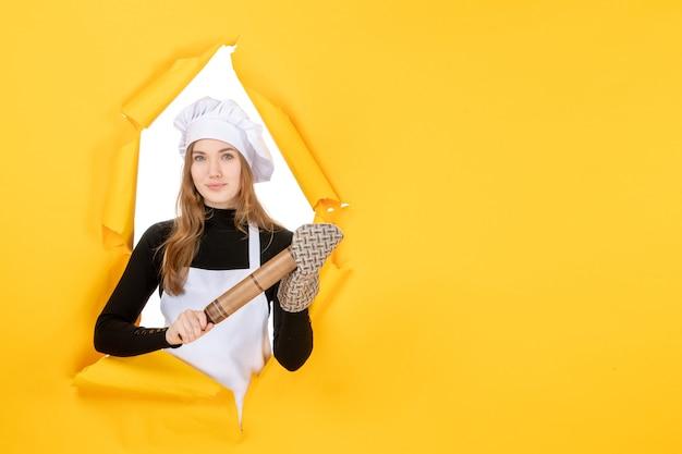 Cuoca vista frontale che tiene il mattarello sulla foto gialla cucina lavoro cucina colore cibo