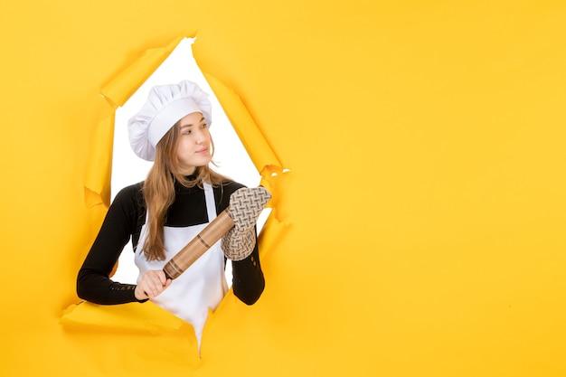 Cuoca vista frontale che tiene mattarello sulla foto gialla cucina lavoro colore cibo sole