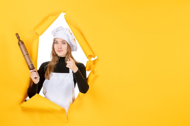 Cuoca di vista frontale che tiene mattarello sul colore giallo del sole cucina lavoro cucina foto emozione