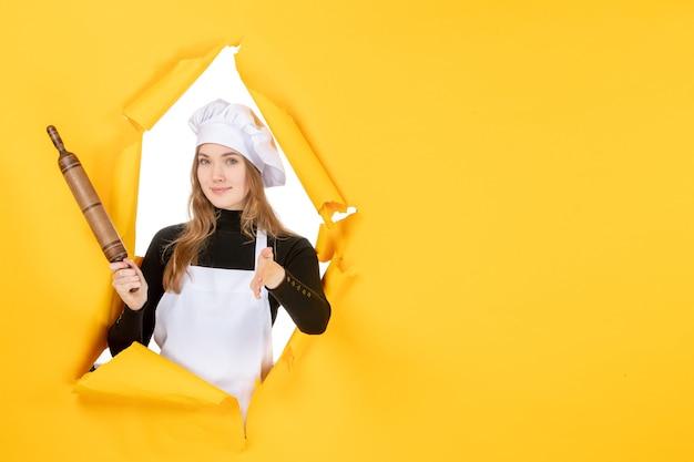 Cuoca vista frontale che tiene mattarello sul sole giallo cibo colore lavoro cucina foto emozione cucina