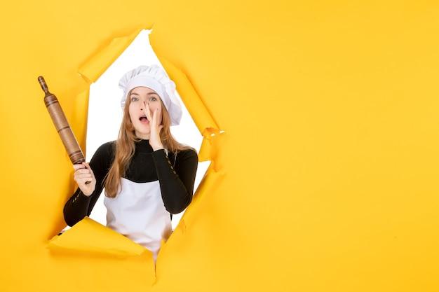 Cuoca vista frontale che tiene mattarello sul sole giallo cibo colore lavoro cucina foto emozione