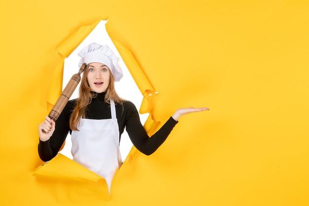 Cuoca vista frontale che tiene mattarello sul sole giallo cibo colore cucina lavoro cucina foto emozioni