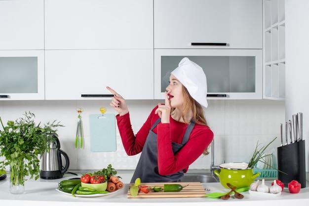 静けさのサインを作るエプロンで正面図の女性料理人