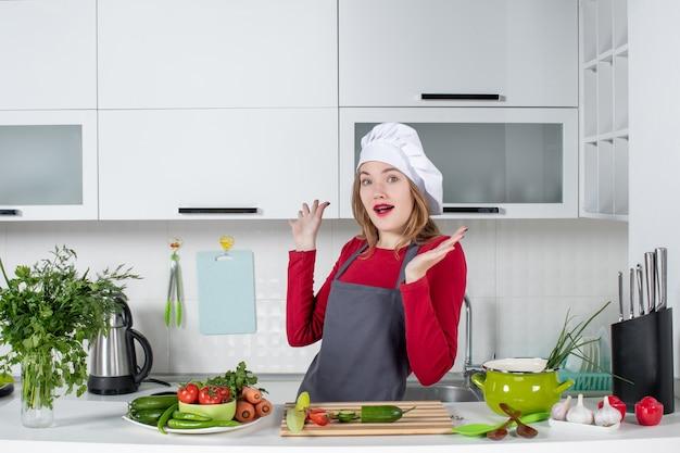 台所のテーブルの後ろに立っているエプロンで正面図の女性料理人