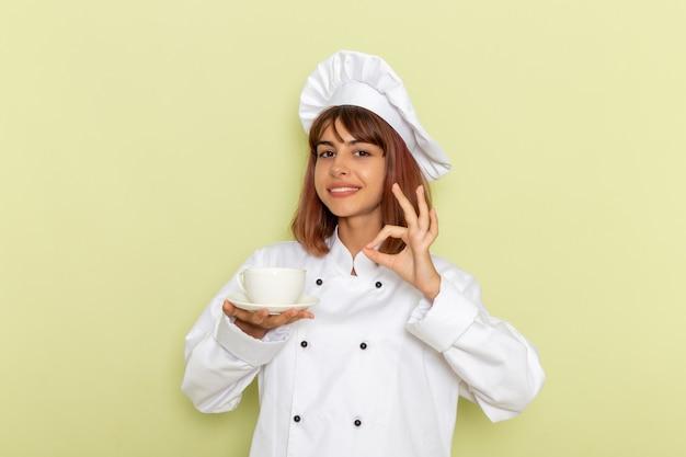 緑の机の上でお茶を飲む白いクックスーツの正面の女性料理人