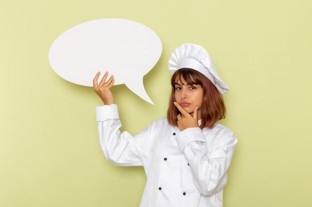 緑の表面に大きな白い看板を保持している白いクックスーツの正面図女性料理人