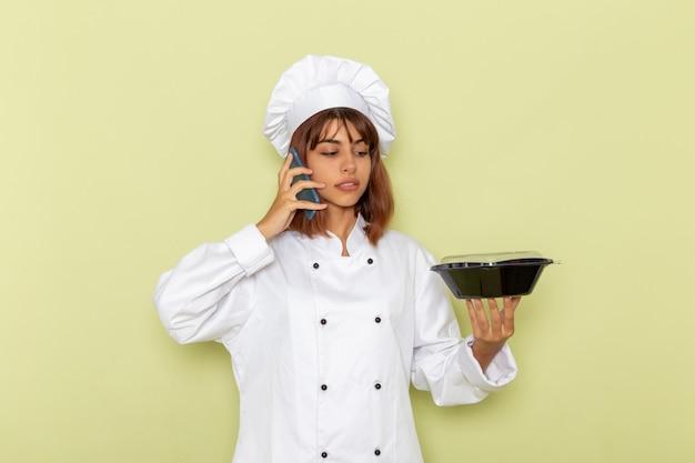 緑の表面に電話で話している黒いボウルを保持している白いクックスーツの正面図女性料理人