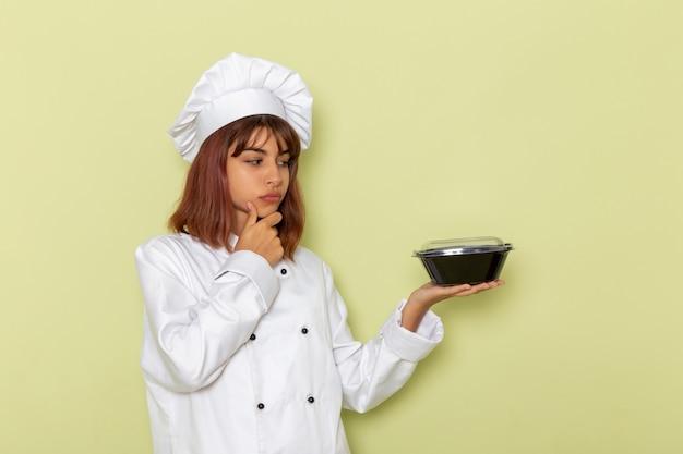 緑の表面にボウルを保持している白いクックスーツの正面図女性料理人