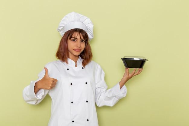 薄緑色の表面にボウルを保持している白いクックスーツの正面図女性料理人