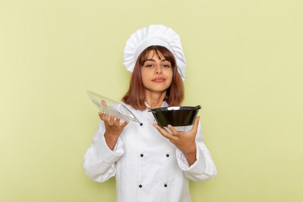 正面図緑の表面に食べ物とボウルを保持している白いクックスーツの女性料理人