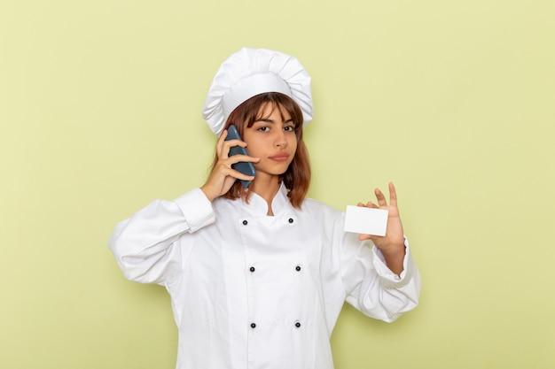 緑の表面で電話で話しているカードを保持している白いクックスーツの正面図女性料理人
