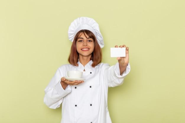 緑の表面にお茶とカードのカップを保持している白いクックスーツの正面図女性料理人