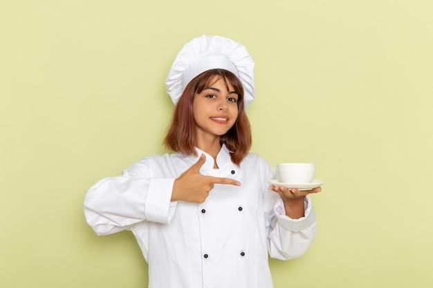 緑の表面にお茶のカップを保持している白いクックスーツの正面図女性料理人