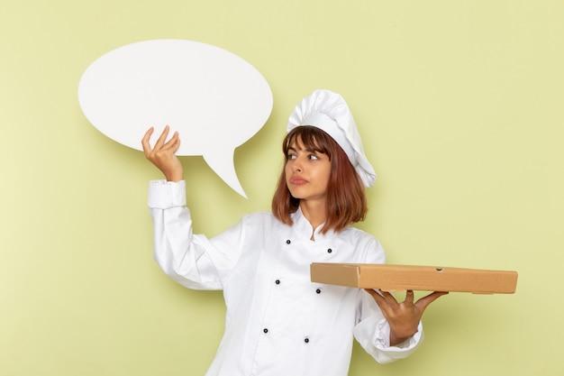 Вид спереди женщина-повар в белом костюме повара держит коробку для еды и белый знак на зеленом столе