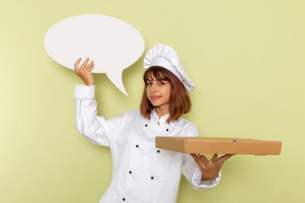 フードボックスと薄緑色の表面に白い看板を保持している白いクックスーツの正面図女性料理人