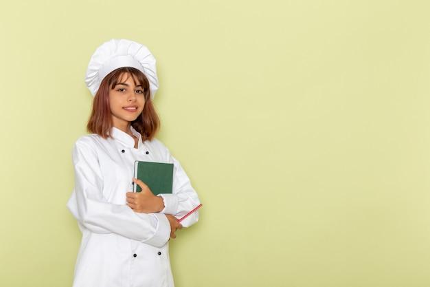 녹색 표면에 녹색 카피 북을 들고 흰색 쿡 정장에 전면보기 여성 요리사